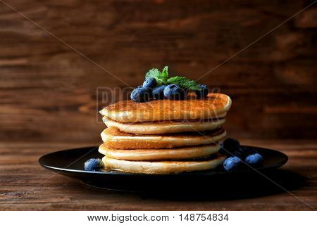Tasty pancakes with blueberries and honey on wooden background