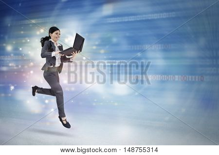 Concept of fast internet connection with young businesswoman running and working in cyberspace with laptop computer