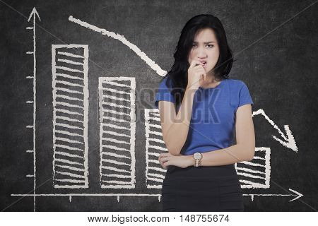 Concept of bankruptcy with a confused businesswoman biting her finger in front of falling graph