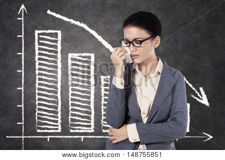 Concept of bankruptcy. Young businesswoman wearing glasses and crying in front of declining chart