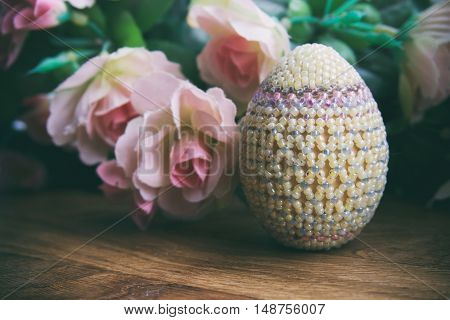 Easter egg from beads next to pink roses