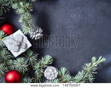 Blue spruce branches with christmas baubles on dark black concrete effect background. Copy space