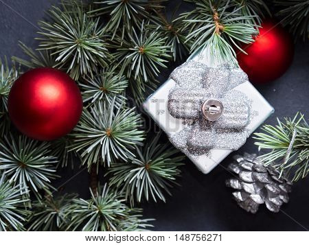 Blue spruce branches with christmas baubles on dark black concrete effect background. Closeup