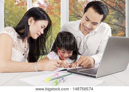 Portrait of a cute little girl studying at home with her parents while writing on the book and using laptop