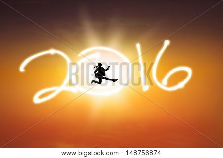 Silhouette of happy businesswoman jumping on the sky with numbers 2016