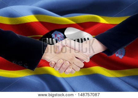 Photo of a friendship handshake with two people hands shaking hands in front of a national flag of Swaziland