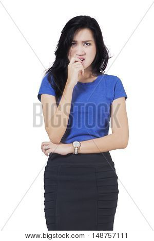 Portrait of a frightened young businesswoman biting her nail isolated on white background