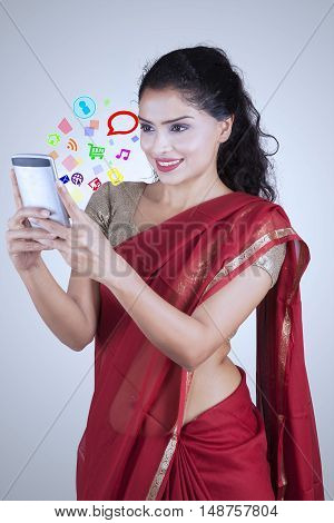 Beautiful Indian woman wearing saree clothes while using smartphone with social media icon