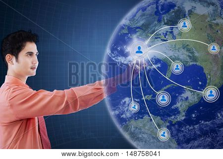 Concept of social network connection. Male Asian entrepreneur touching social network interface on the virtual screen
