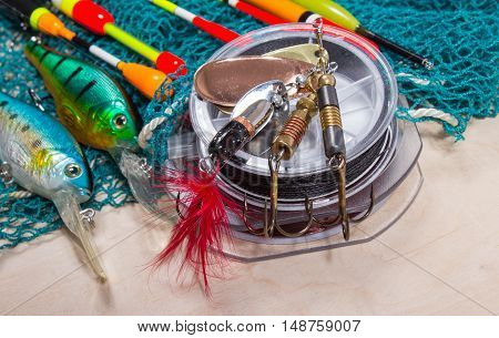 bait wobbler and fishing accessories on wooden background