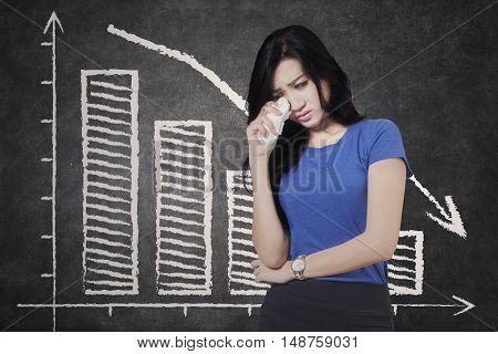 Concept of bankruptcy. Sad businesswoman crying in front of declining graph on the blackboard