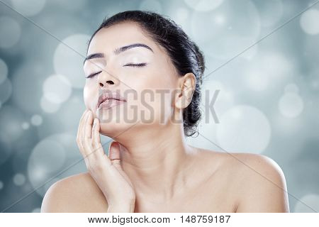 Young female model with natural skin touching her face shot in studio against blur background