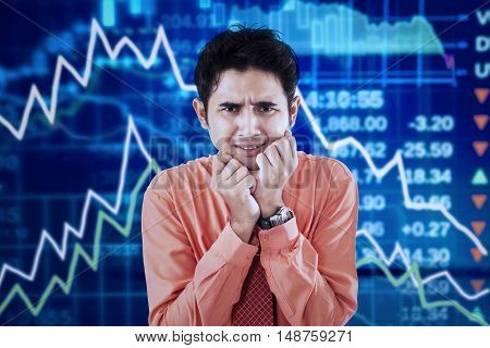 Concept of bankruptcy. Stressful businessman standing in front of declining financial graph