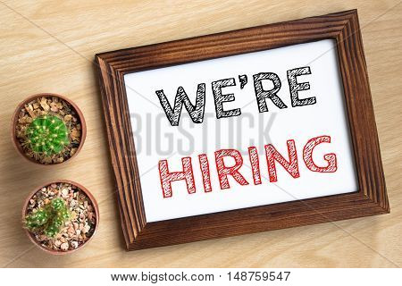 we're hiring, text message on wood frame board on wood table / business concept / Top view