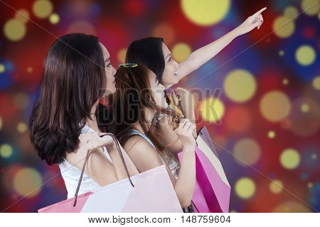 Portrait of three female shoppers pointing at something while carrying shopping bags