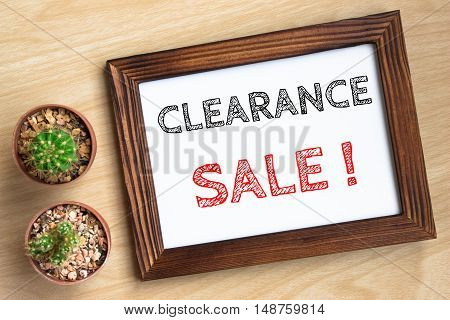 clearance sale, text message on wood frame board on wood table / business concept / Top view