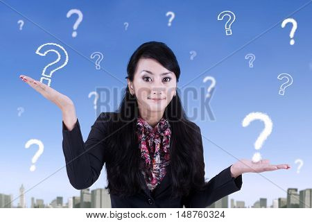 Young Asian businesswoman looks doubt with question marks on the sky