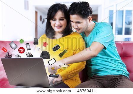 Happy couple buying products online while searching big discount with laptop at home