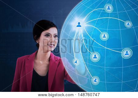 Concept of social media connection with a young businesswoman pressing social media button and globe on the virtual screen