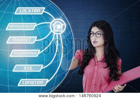 Property value concept. Young Asian businesswoman holding a document and touching property value button on the virtual screen