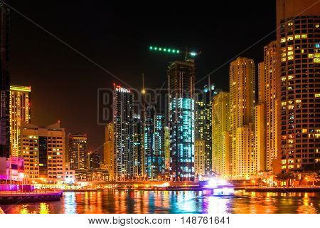 Dubai Marina skyline illuminated at night reflects in the sea. Dubai Marina is a newly futuristic district, famous for touristic restaurants, luxury clubs and nightlife.