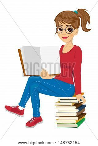 young female student with glasses sitting on a stack of books showing open textbook
