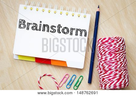 brainstorm, text message on white paper and pencil on wood table / business concept