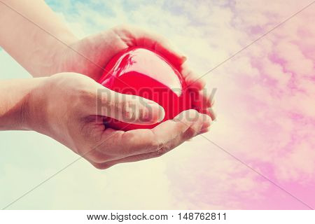 Hand holding red hart on colorful sky, vintage tone