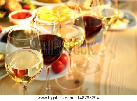Glasses of different wine on wooden table