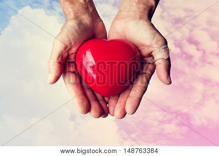 Elderly hands with wound holding red heart heart on colorful sky and white clouds, vintage tone