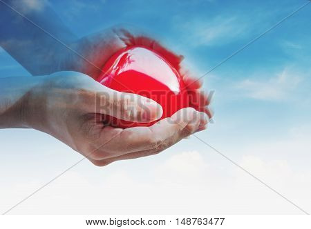 Hand holding red hart with multiple exposure blue sky and white clouds