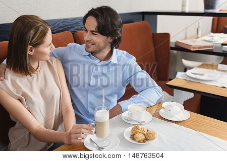 Lost in moment. Attractive young couple enjoying cup of coffee in restaurant, embracing and looking at each other