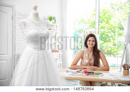 Pretty young dress designer at workplace