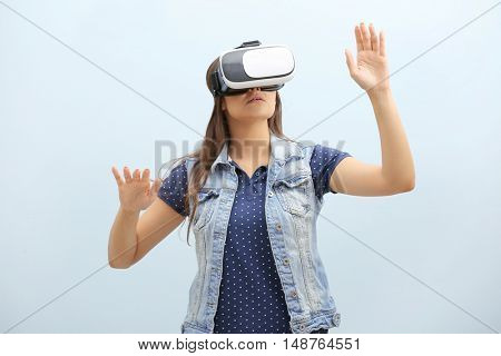 Young woman wearing virtual reality glasses on light background