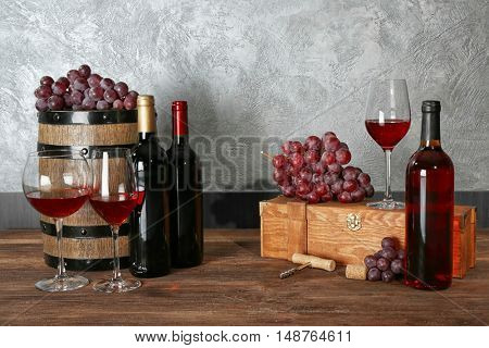 Glasses of red wine, grapes, box and barrel on a wooden table