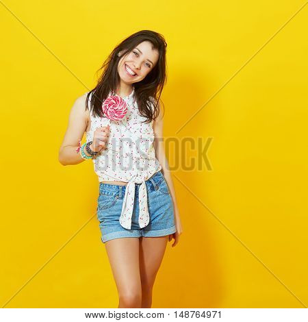 Studio portrait of happy young woman with lollipop over birght yellow wall. Square composition