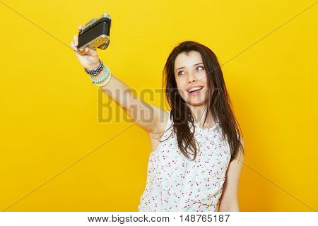 Young woman taking self-portrait  with vintage film camera in studio over vivid yellow background