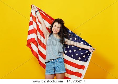 Cheerful teenage patriotic girl holding american flag of the U. S. on yellow background in studio