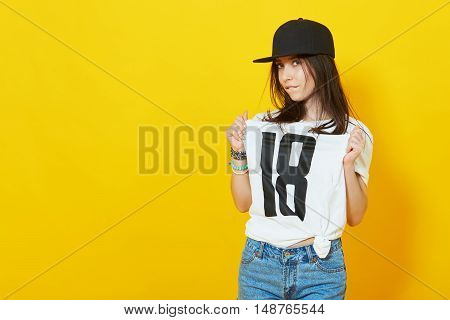 Young beautiful woman posing with white t-shirts with 18 text on it. Girl turned 18 concept. Eighteen years old teenage girl pointing to a tshirt over a bright yellow background.