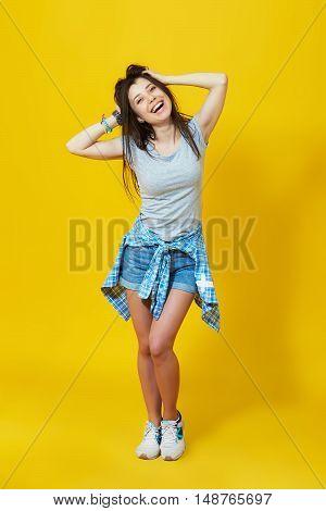 Carefree summer. Laughing beautiful girl posing over yellow background. Full length studio shot of happy teenage woman
