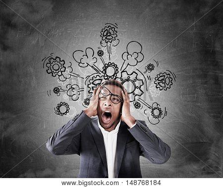 Stressed African Businessman Near Blackboard