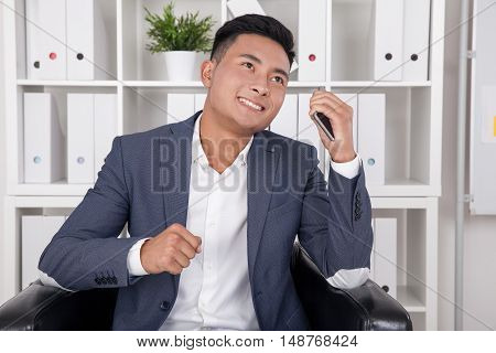 Ecstatic businessman has just ended phone conversation telling about new profitable deal closure. Concept of great business news