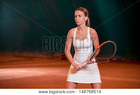Woman playing tennis and waiting for the service