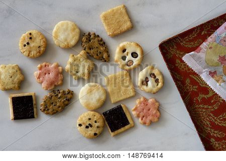 Assorted crisp savoury biscuits, a packet and tray.