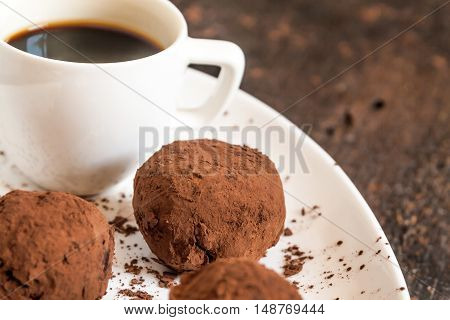 Truffles Sprinkled With Cocoa On Plate With  Cup Of Coffee