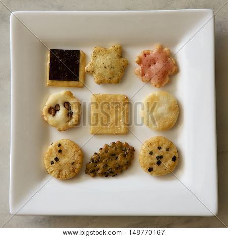 Assorted crisp savoury biscuits on a white plate.