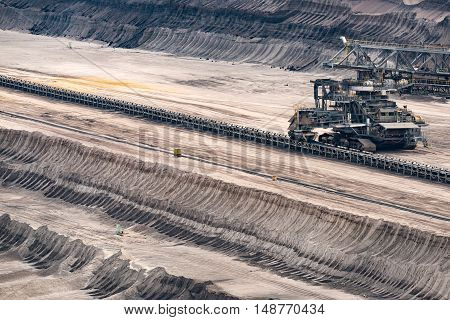 GARZWEILER, GERMANY - SEPTEMBER 16, 2016: Brown Coal is loaded to a long conveyor belt