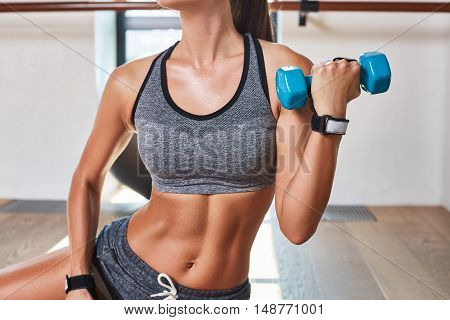 Gorgeous suntanned brunette doing exercises a the gym. girl doing lifting dumbbells. close up