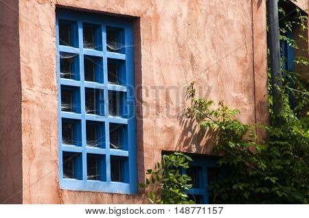 Pink facade of country house with blue windows