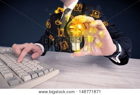 An office salesman promoting his bright ideas concept with illustration of online media and device logos around electric glass light bulb.